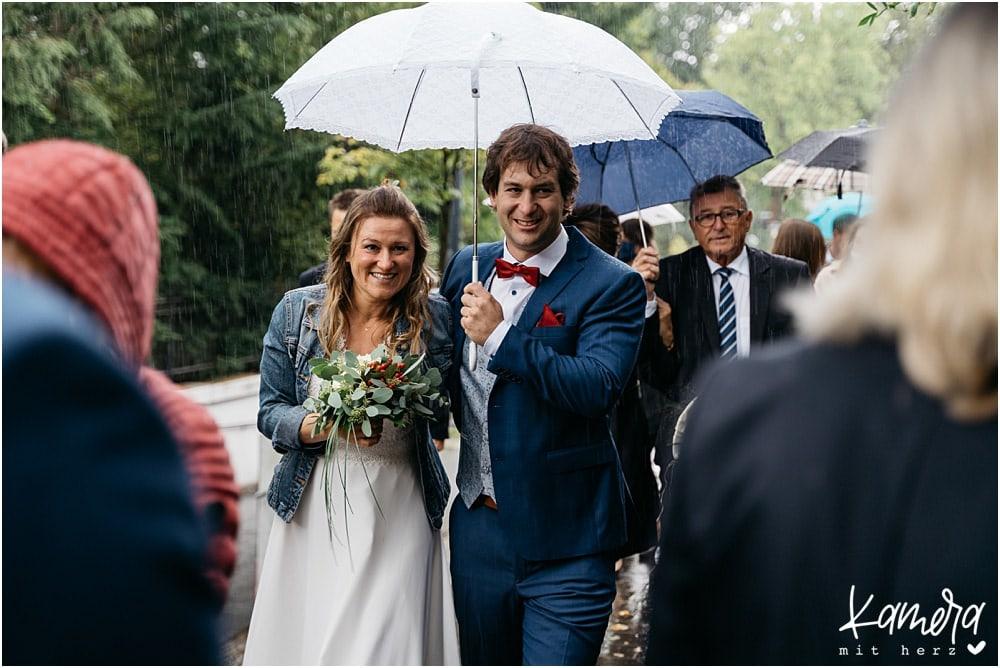 Brautpaar im Regen mit Schirm